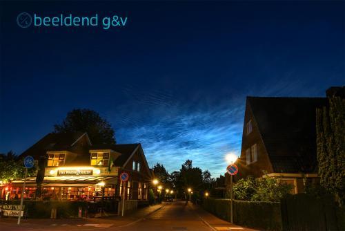 Lichtende nachtwolken boven het Wapen van Huizen