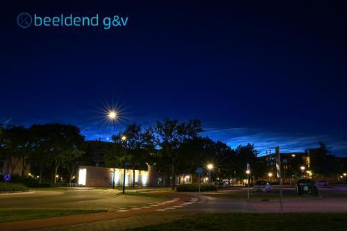 Lichtende nachtwolken boven het gemeentehuis